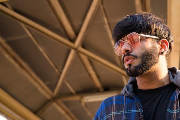 屋外の街の歩道橋で若いハンサムなひげを生やしたインドの流行に敏感な男の肖像画