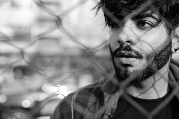 黒と白の屋外の街の通りで若いハンサムなひげを生やしたインドの流行に敏感な男の肖像画