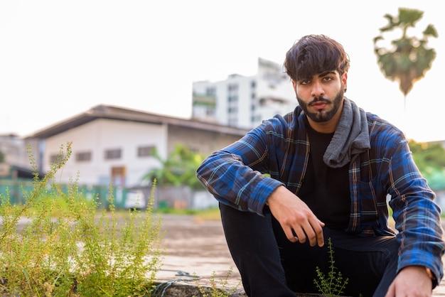 屋外の街の通りで若いハンサムなひげを生やしたインドの流行に敏感な男の肖像画