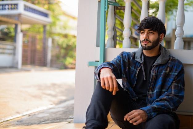 Портрет молодого красивого бородатого индийского хипстера на улице на открытом воздухе