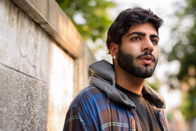 屋外の通りで若いハンサムなひげを生やしたインドの流行に敏感な男の肖像画