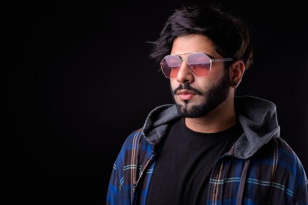 サングラス思考の若いハンサムなひげを生やしたインドの流行に敏感な男の肖像画