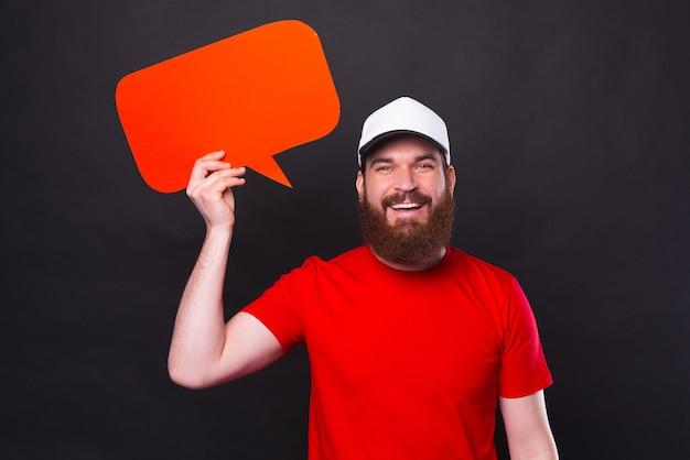 Портрет молодого красивого бородатого мужчины в красной футболке, держащего пустой речевой пузырь и смотрящего в камеру