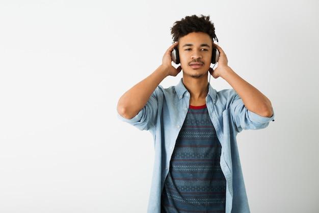白のヘッドフォンで音楽を聴く若いハンサムな黒人男性の肖像画