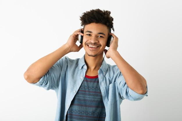Портрет молодого красивого темнокожего мужчины, слушающего музыку в наушниках на белом