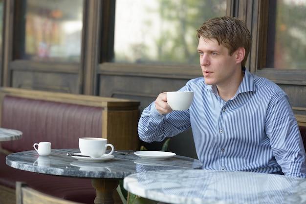 屋外のコーヒーショップでリラックスした若いハンサムな金髪ビジネスマンの肖像画