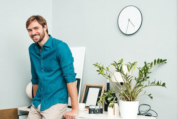 若いハンサムなビジネスマンの肖像画。ブルージーンズのシャツを着た笑顔の男性。紙の机の近くのオフィスでポーズをとってひげを生やしたモデル