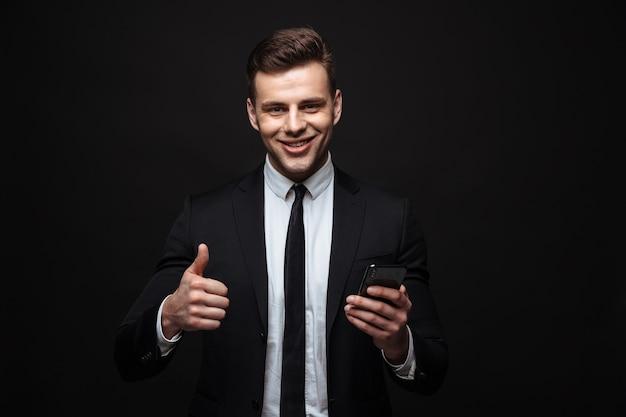 Портрет молодого красивого бизнесмена, одетого в формальный костюм, используя мобильный телефон с большим пальцем вверх, изолированным над черной стеной