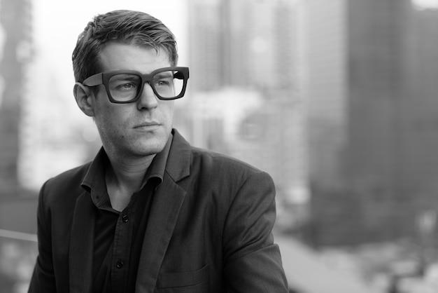 黒と白の街の景色に対してスーツを着た若いハンサムなビジネスマンの肖像画