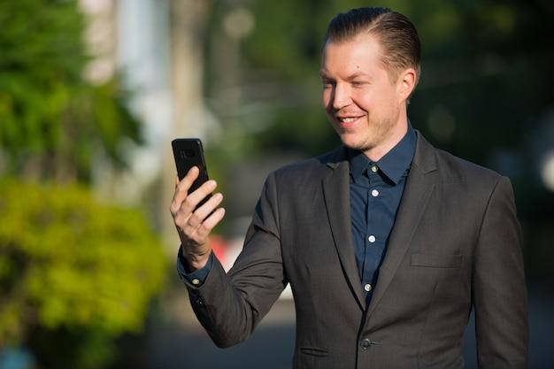 屋外の通りで金髪のスーツを着た若いハンサムなビジネスマンの肖像画
