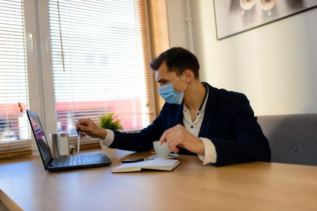 Портрет молодого красивого бизнесмена с лицевой маской в карантине гриппа. фото в кафе с ноутбуком, мобильным телефоном. коронавирус пандемия.