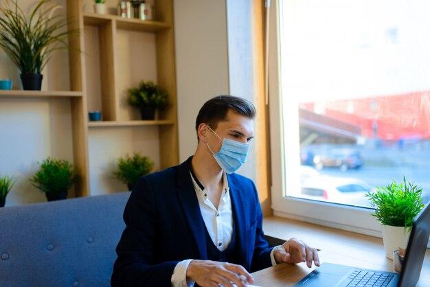 Портрет молодого красивого бизнесмена с лицевым щитком гермошлема в карантине гриппа. фото в кафе с ноутбуком, мобильным телефоном.