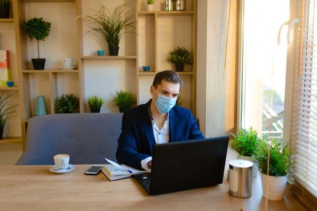 インフルエンザの検疫でフェイスマスクを持つ若いハンサムな実業家の肖像画。