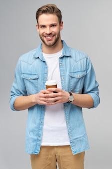 Портрет молодого красивого кавказского человека в джинсовой рубашке, держащего чашку кофе с собой