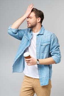 가 서 커피 한잔 들고 청바지 셔츠에 젊은 잘 생긴 백인 남자의 초상화