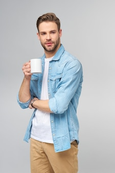Портрет молодого красивого кавказского человека в джинсовой рубашке, держащего чашку кофе