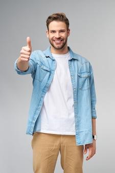 Портрет молодого красивого кавказского человека в джинсовой рубашке, показывающего большой палец вверх жестом стоя