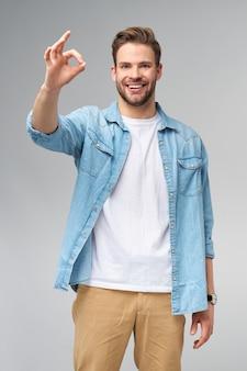 Портрет молодого красивого кавказского человека в джинсовой рубашке, показывающего жест знак ок