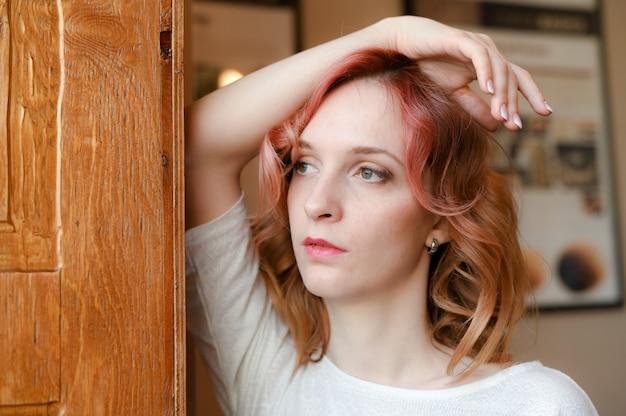 窓の外を見ている若いハンサムな白人赤毛巻き毛の肖像画