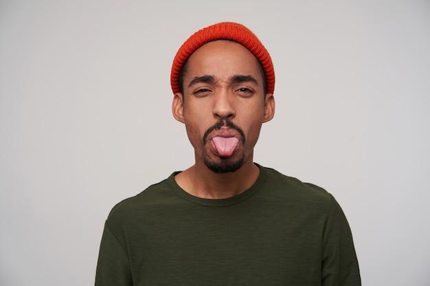 彼の舌を突き出して、カジュアルな服装で白で隔離の赤い帽子の若いハンサムな暗い肌のブルネットの男の肖像画