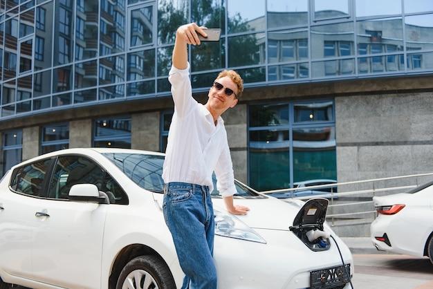 젊은 잘생긴 유럽 남자의 초상화, 전기 자동차에 기대어 스마트폰으로 셀카 사진을 찍고, 무역 쇼핑몰에서 신선한 제품을 구입한 후 도시 발전소에서 배터리를 충전합니다.