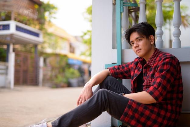 自宅の屋外で若いハンサムなフィリピンの流行に敏感な男の肖像画