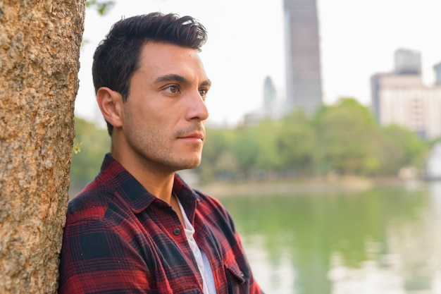屋外の公園で若いハンサムなヒスパニックヒップスターの男の肖像画