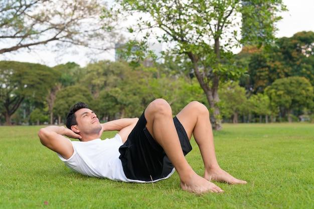 Портрет молодого красавца латиноамериканского происхождения в парке на открытом воздухе