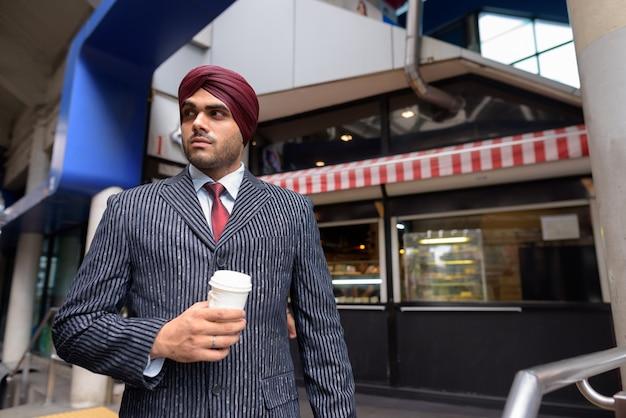 タイのバンコクの街を探索しながらターバンを着ている若いハンサムなインドシーク教のビジネスマンの肖像画