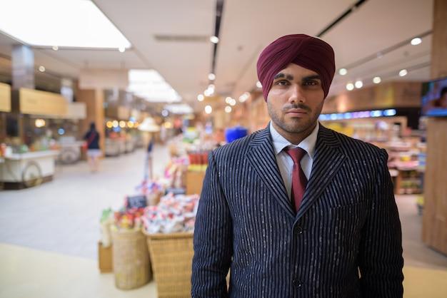 Портрет молодого красивого индийского сикхского бизнесмена в тюрбане во время изучения города бангкок, таиланд