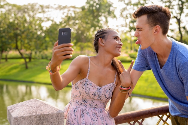 Портрет молодого красивого мужчины и молодой красивой азиатской женщины, расслабляющейся вместе в парке
