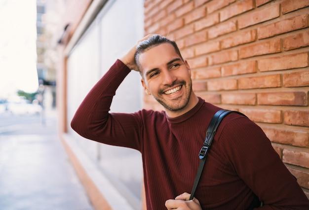 バックパックを背負って、通りのレンガの壁にカジュアルな服を着ている若いハンサムな男の肖像画