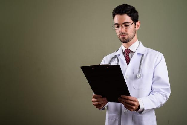 クリップボードを保持している眼鏡と若いハンサムな男の医者の肖像画