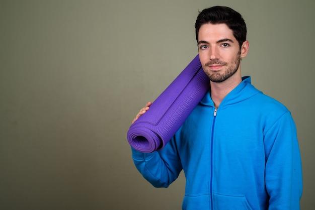 Портрет молодого красивого человека, держащего коврик для йоги, готовый к тренажерному залу
