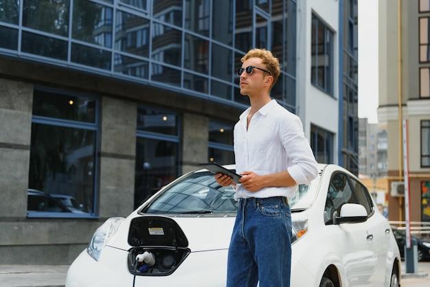 충전소에 서 있는 평상복 차림의 잘생긴 청년의 초상화. 에코 전기 자동차 개념