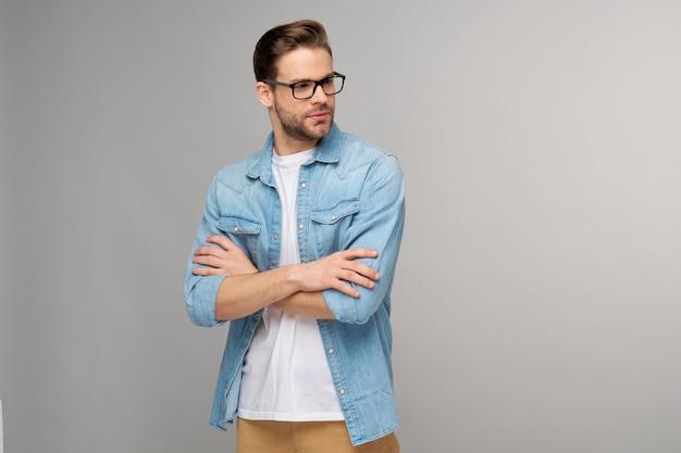 가벼운 벽에 청바지 셔츠에 잘 생긴 젊은이의 초상