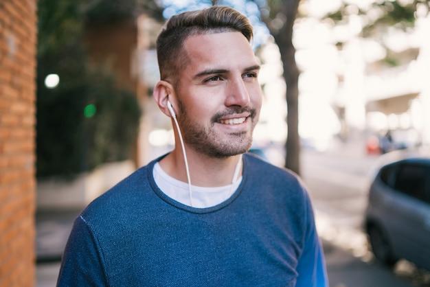 通りで屋外のイヤホンで音楽を聴く若いハンサムな男の肖像画。都市のコンセプト。