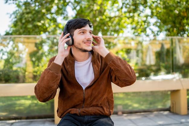 屋外に座っている間ヘッドフォンで音楽を聴く若いハンサムな男の肖像画。都市のコンセプト。