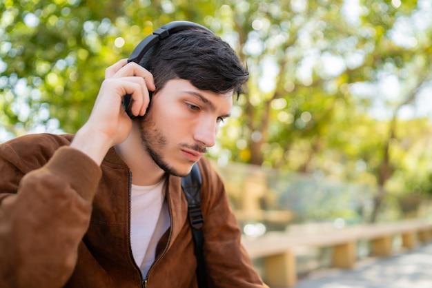 Портрет молодого красивого человека, слушающего музыку в наушниках, сидя на открытом воздухе. городская концепция.