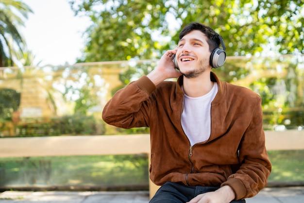屋外に座ってヘッドフォンで音楽を聴いている若いハンサムな男の肖像画。アーバンコンセプト。