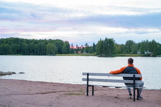 호수보기에 벤치에 앉아 젊은 잘 생긴 남자의 초상화