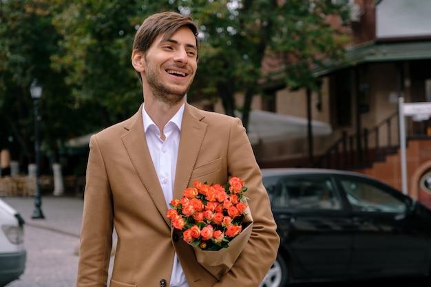 バラの花束を持って笑っている若いハンサムな男の肖像