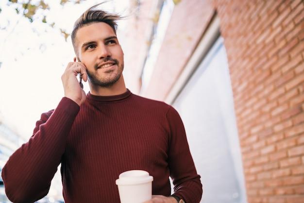 通りで屋外のコーヒーカップを押しながら電話で話している若いハンサムな男の肖像画。コミュニケーションの概念。