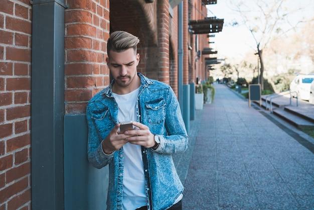 通りで屋外に彼の携帯電話を使用して若いハンサムな男の肖像画。コミュニケーションの概念。