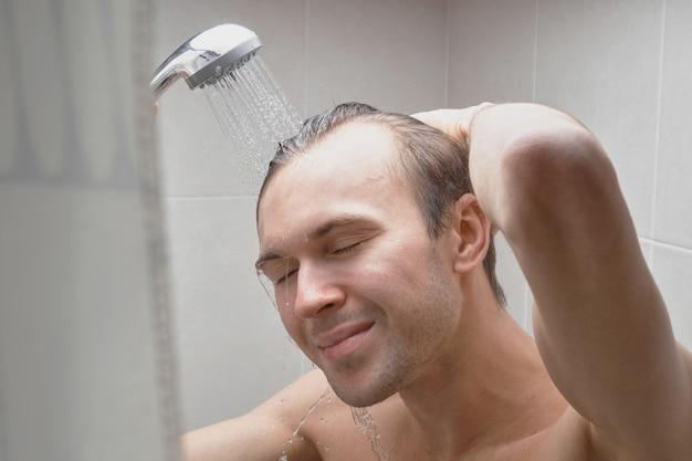 若いハンサムな男の肖像画はシャワージェルで自分自身を洗い、自宅のクローズアップのバスルームでシャンプーで頭を泡立てます