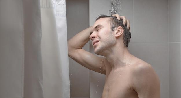 Портрет молодого красавца умывается гелем для душа, намыливает голову шампунем в ванной комнате дома крупным планом