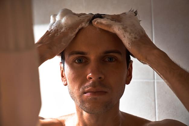 Портрет молодого красавца умывается гелем для душа, намыливает голову шампунем в ванной комнате дома крупным планом Premium Фотографии
