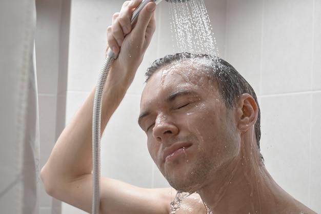 Портрет молодого красавца умывается гелем для душа, намыливает голову шампунем в ванной