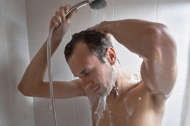 若いハンサムな男の肖像画はシャワージェルで自分自身を洗い、バスルームでシャンプーで頭を泡立てます
