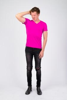 Портрет молодого красавца в фиолетовой рубашке у белой стены